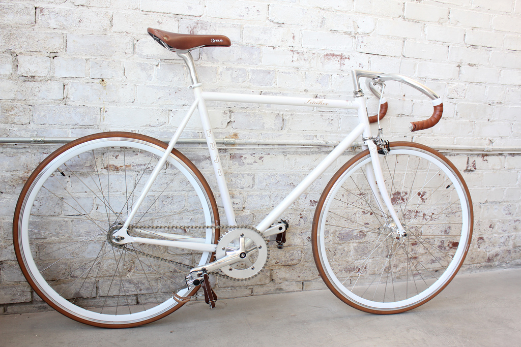 White Bike With Brown Trim And Seat Leaning Against Wall