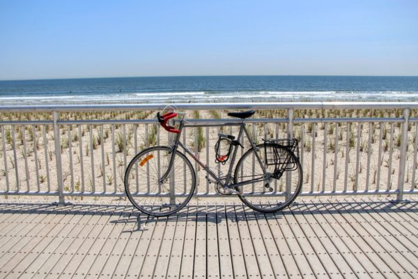 Bike parked along fence at a Queens beach, waves gently lapping ashore in the background
