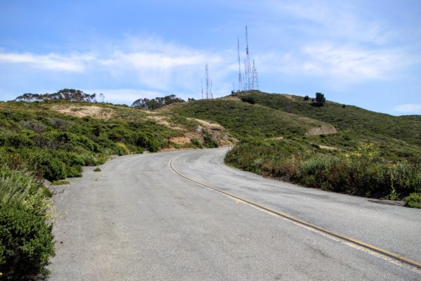 Winding road leading to the top of San Bruno Mountain State Park, satellite and antenna towers can be seen at the summit, sunny day, green brush on either side of the road