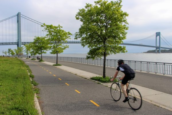 Cyclist rides along the Shore Parkway bike path, nearing the Verrazano-Narrows Bridge