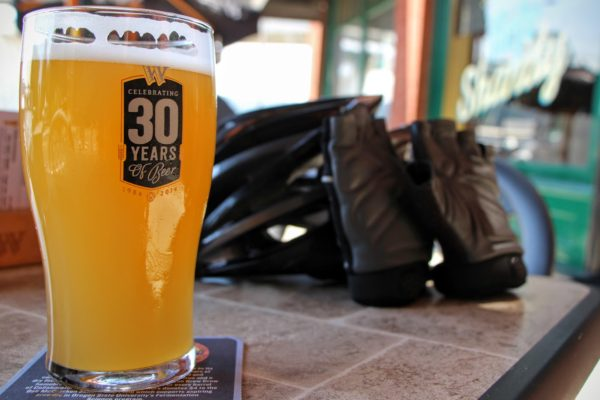 Closeup of beer in a beer glass with biking gloves leaning on a bike helmet, taking a break during a Portland brewery tour