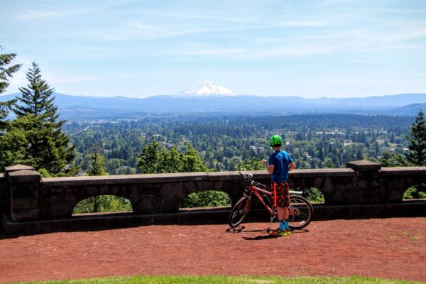 Young cyclist stands atop Rocky Butte looking out towards Mt. Hood on a beautiful sunny day