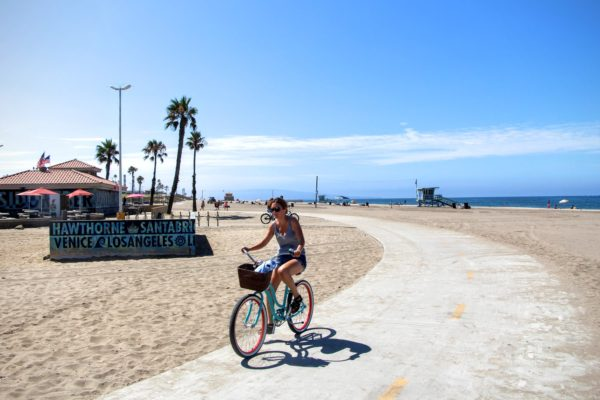 Girl rides a beach cruiser along the Marvin Braude Bike Trail, Palm trees and ocean in the background