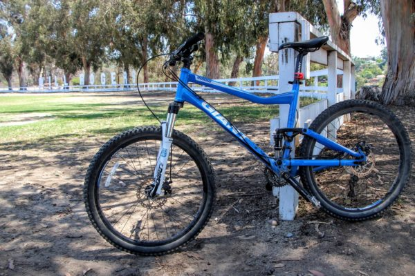Blue bike parked against white fence at entrance to Will Rogers State Park