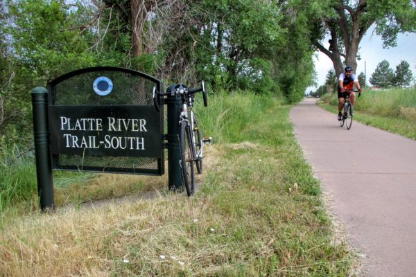 Cyclist rides on the South Platte River Trail, green grass and a bike parked against a sign with the trail's name written on it