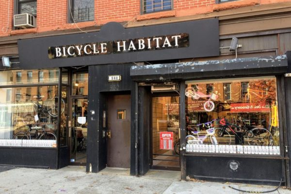 Exterior image of a bike shop in nyc, red brick building with Bicycle Habitat written above doorway