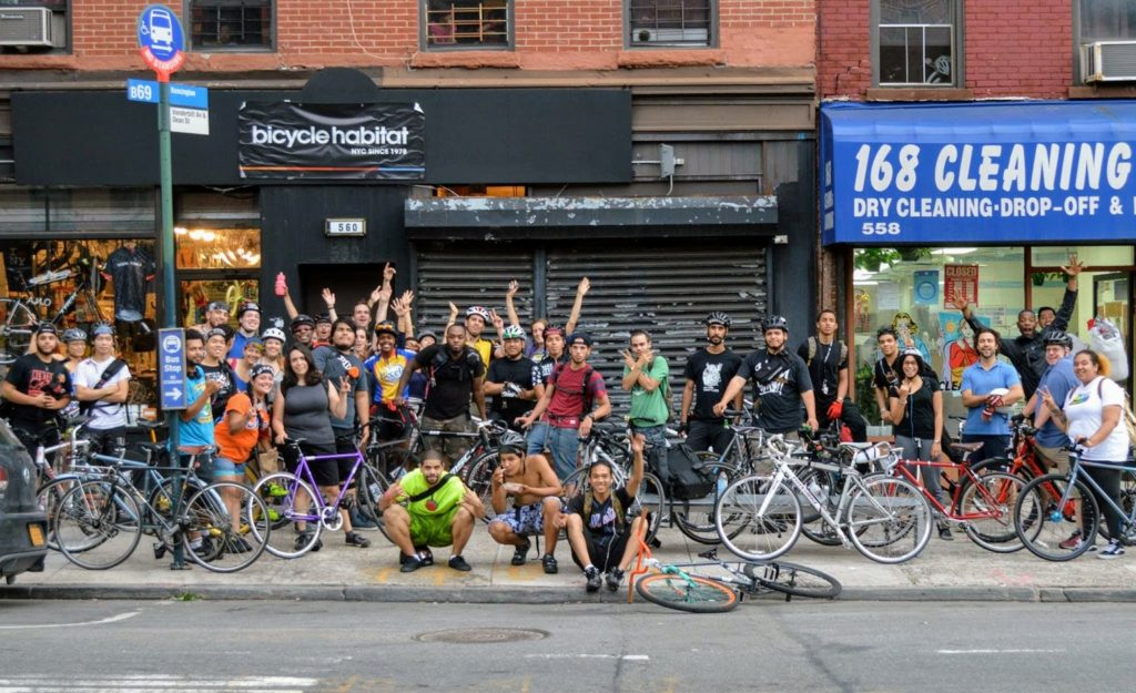 Large group of cyclists raises arms in celebration in front of Bicycle Habitat bike shop in NYC