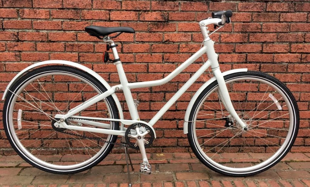 A Spinlister member's grey IKEA SLADDA bike leans against a red brick wall