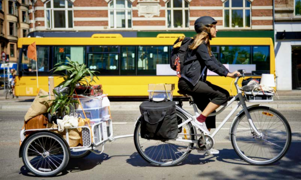 Girl rides IKEA SLADDA bike in the street, towing a trailer filled with items, A bus passes behind her