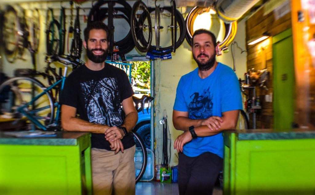 Two owners of Bayou City Cycles pose behind the green counter in their shop.