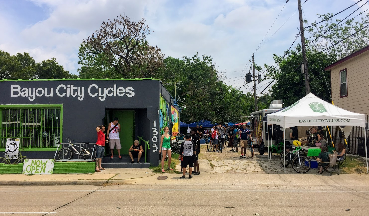 Bayou City Cycles storefront with many people out front, along with a food cart and tent next to the building