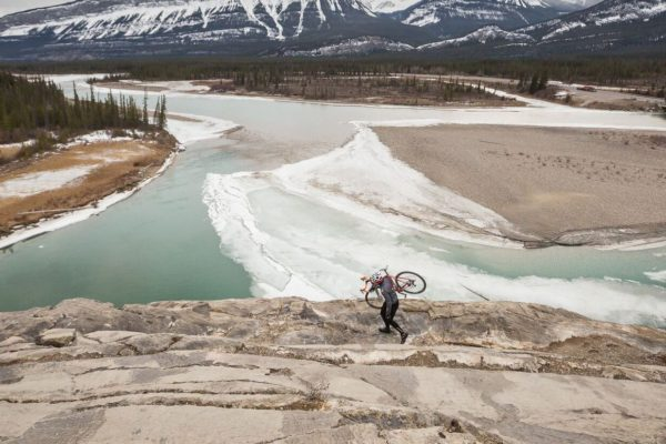 Cyclist carries his bike over rocks with mountains in the background while participating in bicycle tourism in Canada