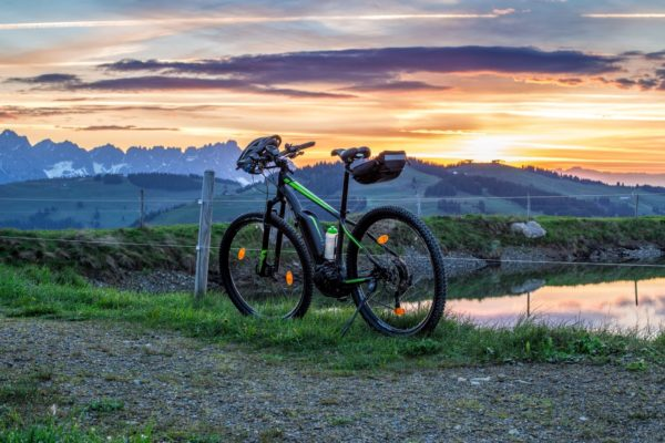 Electric bike leaned against fence at sunset with mountains in the background