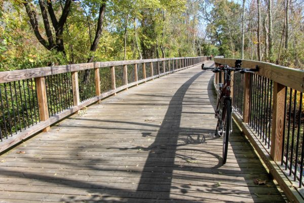 Bike leans against wooden hand rail on a wooden bridge along the Mount Vernon bike trail