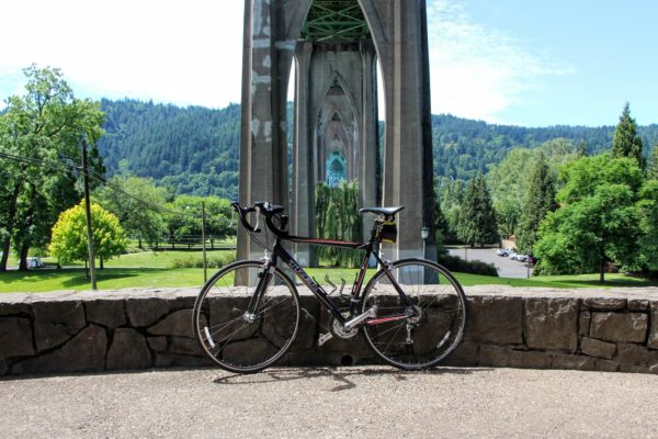 Portland bike routes photo of a bike parked under Portland's famous St Johns Bridge on a sunny day with green trees in the background