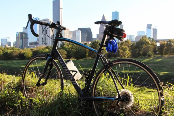 Bike on green grass with downtown Houston, the next American cycling capital, in the background
