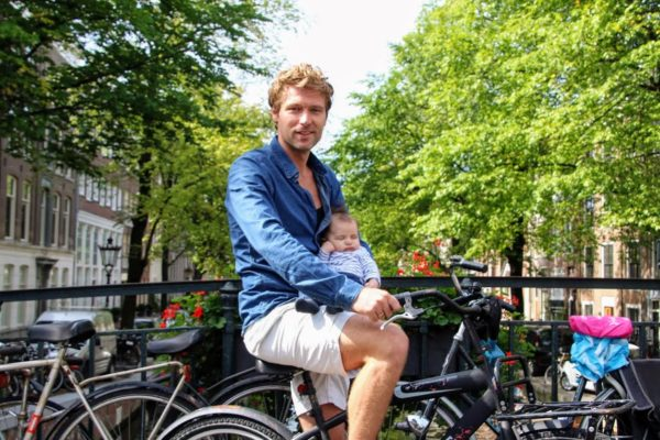 man sits atop bike with baby in arms in amsterdam bike sharing scene