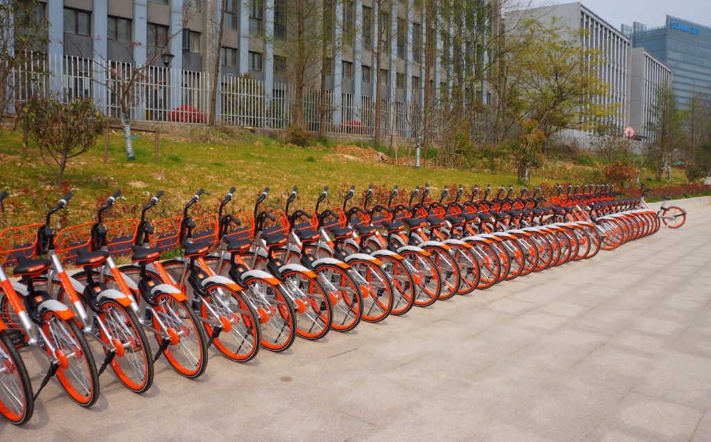 Pile of identical Chinese bikes parked in front of a building