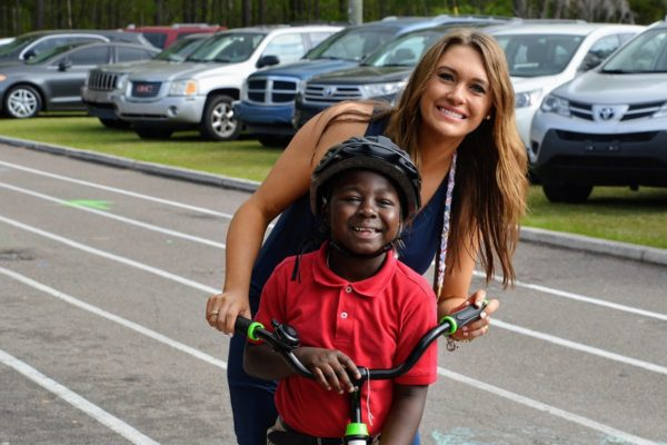 Katie Blomquist, director of Going Places nonprofit, stands behind one of her students on his bike in a parking lot