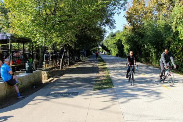 Two cyclists ride the Katy Trail Dallas on a sunny day with trees on either side of them