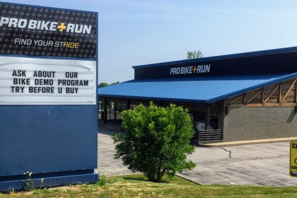 Exterior of Pro Bikes + Run, one of four Pittsburgh bike shops with this name, with a blue roof and sign posted out front indicating rental demo program