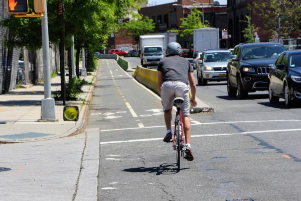 Urban cycling commuter pedaling next to cars about to enter a divided bike lane in Brooklyn