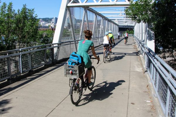 Bicycle tax cyclists bike across pedestrian bridge on sunny day in Portland