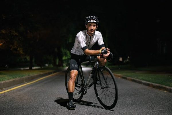 Cyclist on a dark city street illuminated by overhead street light sits atop bike offering bike tips about New York City