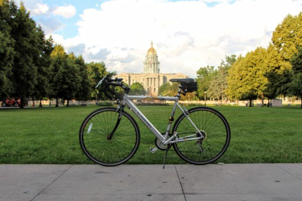 Bike parked in front of Colorado State House on Denver bike trails with trees on the side and a large field in front of the building