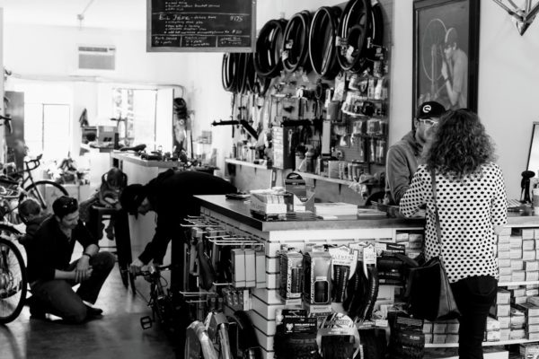 Customers shop at front counter of a local Denver cycling shop