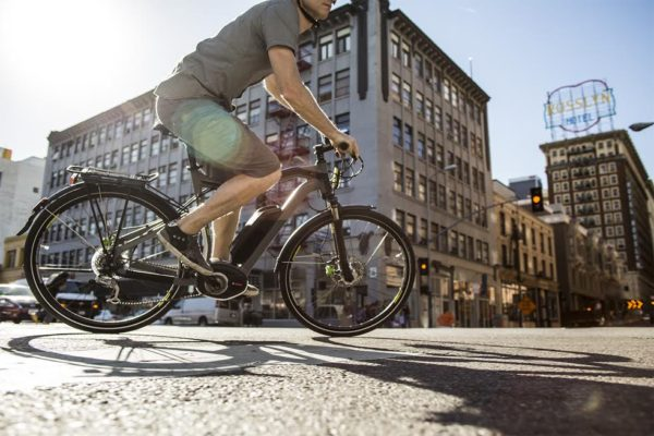 Man in shorts rides e-bikes around a city street with buildings in background