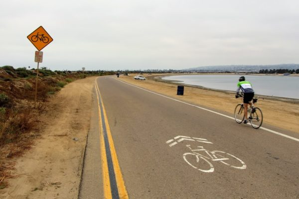 Cyclist rides around Fiesta Island with bike signs visible and beach and water on the right side of photo