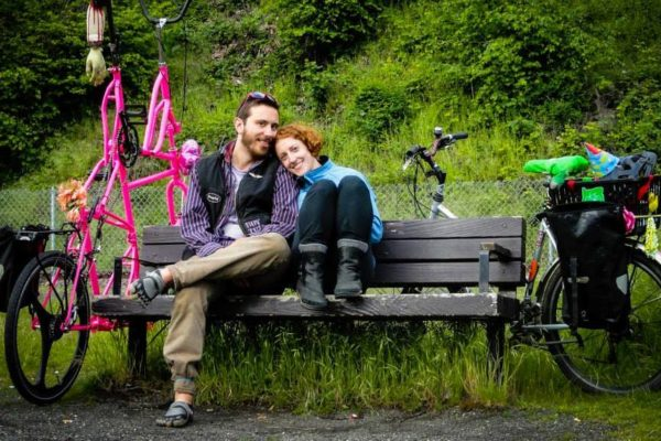 Portland bike sharing couple sits on bench with large pink bike to the left and standard gray bike to the right