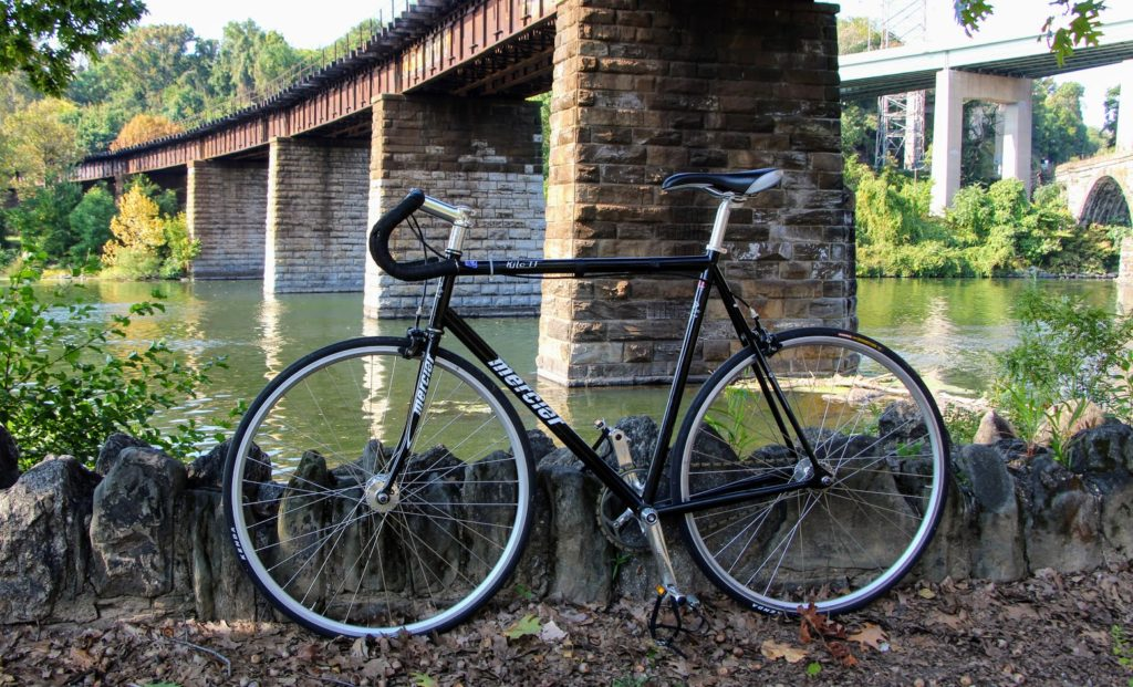 Black bike parked in front of a stone bridge along Philadelphia's Schuylkill River Trail