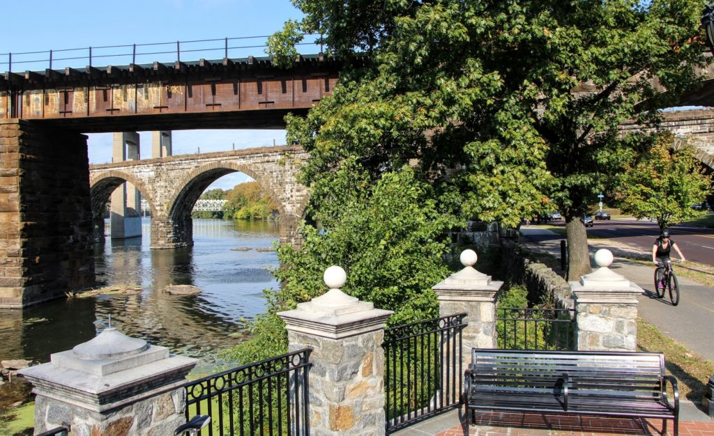 Cyclist bikes along Schuylkill River Trail on sunny day with three old bridges visible crossing the river on the left side of the photo