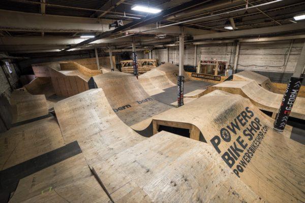 Indoor bike park jump room with multiple wood ramps inside a warehouse